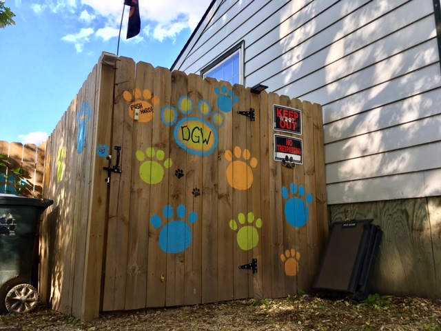 Fence around dog daycare, pawprint logos painted on